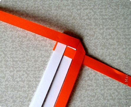 Возьмите две полоски, согните пополам. Пропустите один конец полоски (у меня красный) между белыми. фото 5
