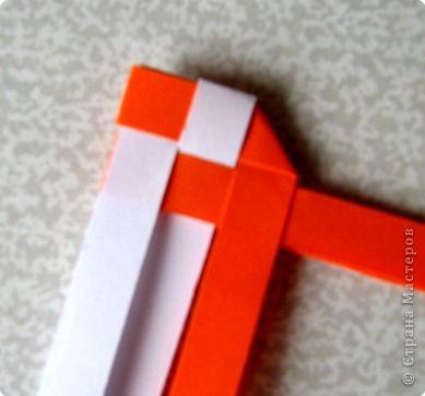 Возьмите две полоски, согните пополам. Пропустите один конец полоски (у меня красный) между белыми. фото 7