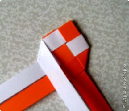 Возьмите две полоски, согните пополам. Пропустите один конец полоски (у меня красный) между белыми. фото 13