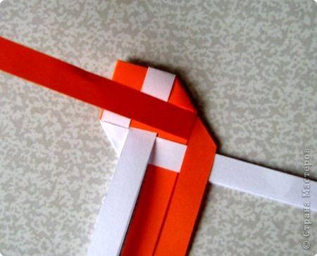 Возьмите две полоски, согните пополам. Пропустите один конец полоски (у меня красный) между белыми. фото 15
