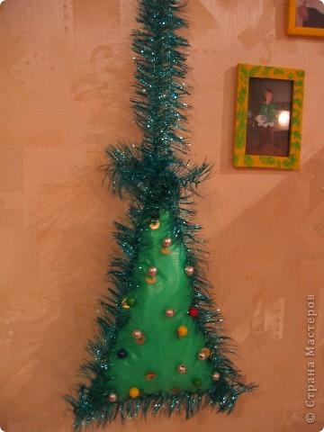 Первая елочка, это поделка для детского сада на уличную елку, высота без петельки 30см. Изготовлена она из клеенчатой скатерти, вырезаны два треугольника, прошито степлером и внутрь сын набил ломаный пенопласт, , край зашит аналогично, пришпилена мишура из хвостика которой  сделана петелька высотой около 20 см., пайетки и бусинки пришиты леской. (извиняюсь за ночную съемку)   фото 1