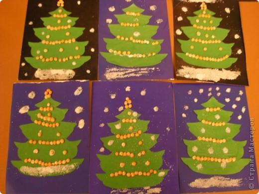 Работы детей старшей группы детского сада. Нарядные елочки.  Дети украшают шаблоны елочек половинками гороха, снег-манка. фото 1