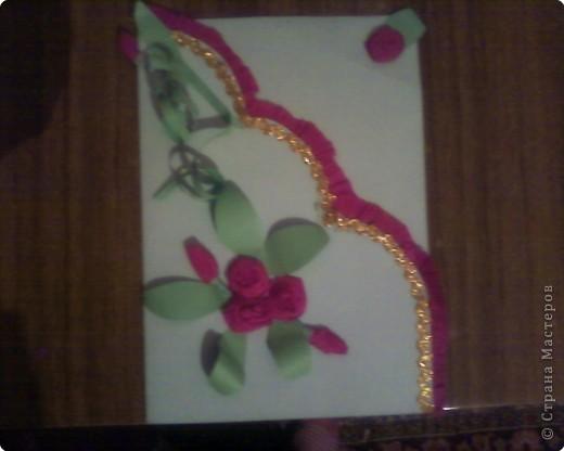На двухстороннем  цветном листе бумаги (картонном) Срезаем на искосок верхнюю часть листа (заранее согнутого в  пополам) на края складываем гармошкой гофрированую бумагу и приклеиваем на двухсторонний скочь, чтобы не видно было погрешностей рядышком приклеиваем блестящую ленточку. Розочки накручиваем из гофрованой бумаги, и вырезаем зеленые листики   фото 1