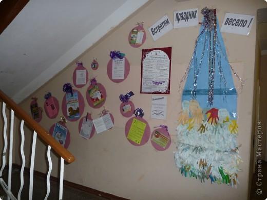 """Новогодняя елка из детских ладошек, на которую свою """"лапу"""" мог приклеить любой ученик. Россыпь бумажных елочных шаров с наклеенными анонсами новогодних конкурсов и спектаклей - так была оформлена в этом году одна из стен в школе."""