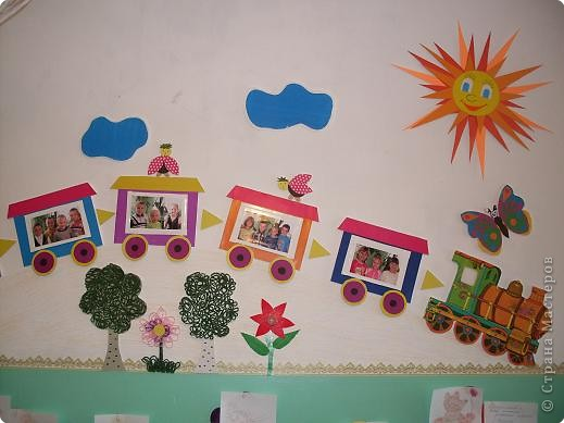 Поезд в раздевалке, с фотографиями детей. Вагоны наклеяны на пенопласт, для объема. Поезд спускается с горки, под горкой деревья. фото 1