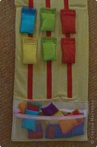 Эту идею нашла где-то у интернете (к сожалению, не помню где), исполнение моё. Это игровое поле из ткани с нашитыми на него лентами-липучками ( та их часть на которую лепят). И мешочки из капроновых лент для волос по цветам радуги. По два мешочка на каждый цвет. фото 4