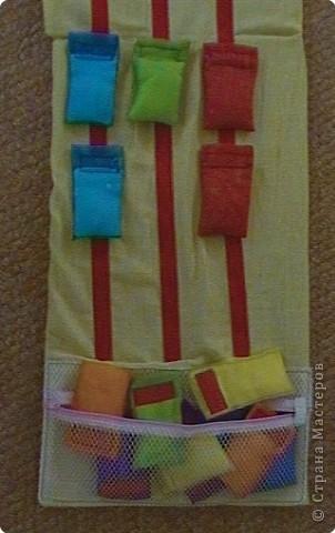 Эту идею нашла где-то у интернете (к сожалению, не помню где), исполнение моё. Это игровое поле из ткани с нашитыми на него лентами-липучками ( та их часть на которую лепят). И мешочки из капроновых лент для волос по цветам радуги. По два мешочка на каждый цвет. фото 5