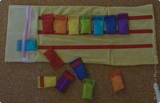 Эту идею нашла где-то у интернете (к сожалению, не помню где), исполнение моё. Это игровое поле из ткани с нашитыми на него лентами-липучками ( та их часть на которую лепят). И мешочки из капроновых лент для волос по цветам радуги. По два мешочка на каждый цвет. фото 3