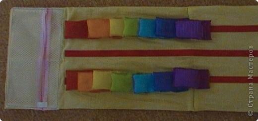 Эту идею нашла где-то у интернете (к сожалению, не помню где), исполнение моё. Это игровое поле из ткани с нашитыми на него лентами-липучками ( та их часть на которую лепят). И мешочки из капроновых лент для волос по цветам радуги. По два мешочка на каждый цвет. фото 1
