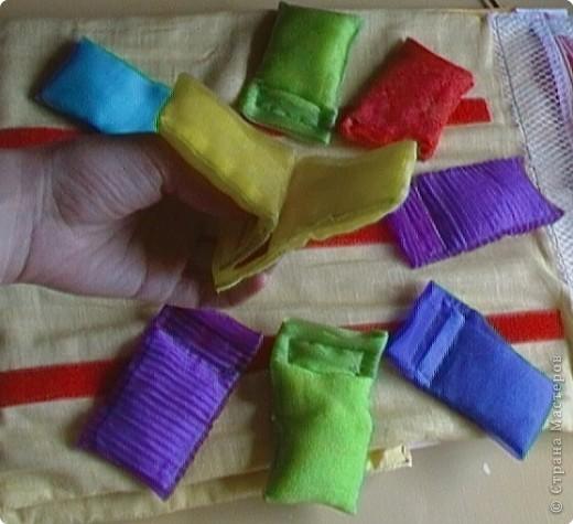 Эту идею нашла где-то у интернете (к сожалению, не помню где), исполнение моё. Это игровое поле из ткани с нашитыми на него лентами-липучками ( та их часть на которую лепят). И мешочки из капроновых лент для волос по цветам радуги. По два мешочка на каждый цвет. фото 6