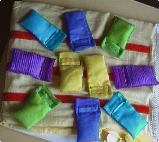 Эту идею нашла где-то у интернете (к сожалению, не помню где), исполнение моё. Это игровое поле из ткани с нашитыми на него лентами-липучками ( та их часть на которую лепят). И мешочки из капроновых лент для волос по цветам радуги. По два мешочка на каждый цвет. фото 8