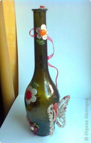 Первая попытка украсить бутылку. Бабочку сделала из сломанной заколки-краба, цветочки из пуговиц. Рядом с каждым цветом листочек из бисера. фото 1