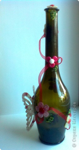 Первая попытка украсить бутылку. Бабочку сделала из сломанной заколки-краба, цветочки из пуговиц. Рядом с каждым цветом листочек из бисера. фото 2