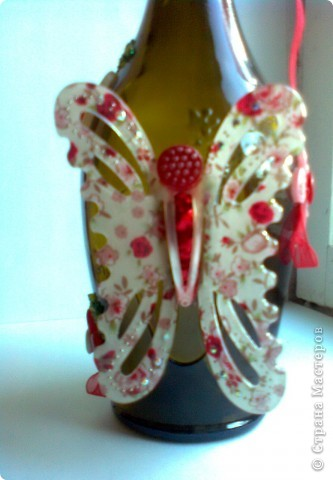 Первая попытка украсить бутылку. Бабочку сделала из сломанной заколки-краба, цветочки из пуговиц. Рядом с каждым цветом листочек из бисера. фото 3