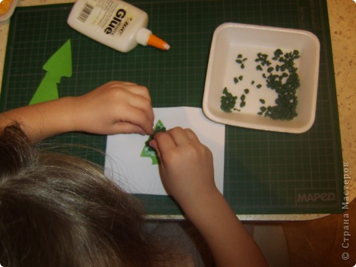 Вот снова делали с детками открытку, в новой технике. Похожа на технику торцевания, как то пробовали с детками им не понравилось. И тут как то делала урок для малышей, из салфеток делали рыбку. Возраст малышей был 1,5-2. Мы просото порвали, помяли разноцветные салфетки и скатали из них кружки. Так же поиграли, сделали упражнение для лёгких : раскрываете салфеточку и начинаете дуть, устаивали конкурс кто дальше салфеточку отдует от этого занятия детки были в восторге.   Данная техника развивает мелкую моторику, а упражнение для лёгких укрепляет лёгкие и бронхи а так же помогает выводить мокроту из лёгких.    Дальше продолжили делать нашу рыбку на большой шаблон рыбки нарисованый от руки ( 1,0мх0,7м), мы стали клеять при помощи клея карандаша наши шарики из салфеток. К сожалению фото не сделала.   И вот решила сделать в этой технике ёлочки, колокольчик и других. Только в миниатюрном виде. И решила поделится с данной техникой с мамочками. Моим деткам очень понравилось рвать и делать шарики. Правда кухня была засыпана ими везде. Но зато посмотрите каие открыточки у нас получились.   фото 7