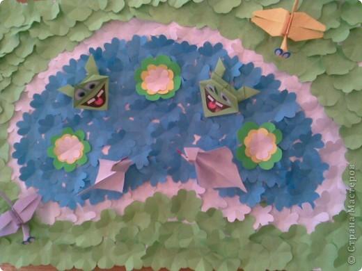 """На уроке труда ребята вырезали цветы. Решили из вырезанных цветов сделать какую-нибудь поделку. Идею сюжета взяли здесь в Стране Мастеров ( поделка """"Пруд с лягушками""""). Мы сделали свое озеро и полянку из этих цветов, а лягушки, стрекозы и лебеди - оригами."""