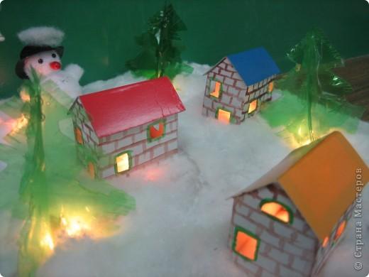 Деревенька зимой. Выполнен макет на картонной основе. Снег- вата; домики склеены из бумаги; елочки из пластиковых бутылок; снеговик из нитяных помпонов+ шапочка крючком. фото 2