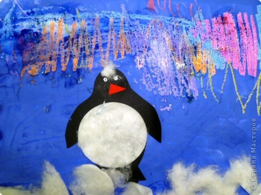 С большим удовольствием смотрели видеоролик о северном сиянии, а потом делились впечатлениями… На севере вечная зима, царство снежных туманов и удивительной красоты полярных сияний.  Кто живет в этом суровом холодном краю? Кто чаще всех любуется северным сиянием?  Конечно, это белые медведи и пингвины.  Восковыми мелками нарисовали-почиркали сияние… Для фона выбрали синий цвет… Пингвина пора на место… пузико - ватный диск… Снег, белый пушистый… тоже ватный диск… А почему бы сиянию не придать блеска? Гель - блестки подойдут…   фото 2