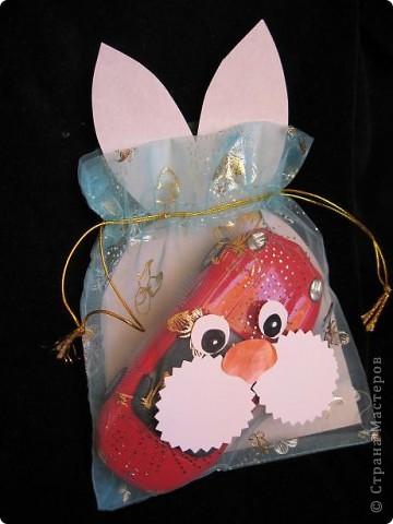 Вот так можно упаковать небольшой подарок маленькому мальчику. На стилизованной открытке с ушками можно написать новогодние пожелания, а изображение зайчика на мешочке принесет счастье в Новом году.  фото 1