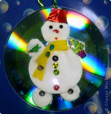Почему бы не сделать елочную игрушку?  Снеговик самый подходящий персонаж для моих трехлеток. Ватные и лазерные диски вот что нам нужно! Снеговик кругленький, мягонький, беленький. А вокруг северное сияние, переливается всеми цветами радуги.   фото 2