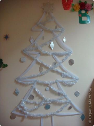 Вот такая ёлочка выросла у нас на стене в приёмной. Полоска шифона (остатки от пошива штор), картон , обёрнутый пищевой фольгой  и мишура. Вот и все составляющие елки. Может идея сгодится кому-нибудь. фото 1