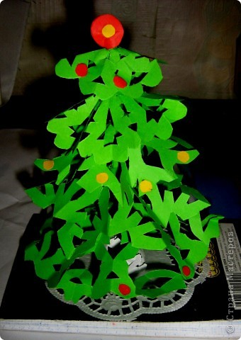 Ёлочку сделала минут за 15, навырезала 5 снежинок из зелёной бумаги разного размера. На спицу намотала бумагу, потом убрала спицу, получила тонкий ствол, а теперь начиная снизу надеваем снежинки, а под ними накручиваем небольшой валик из полоски, чтобы наши снежинки были неподвижны. Укращаем цветными шариками! фото 1
