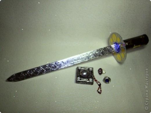 Вот и меч к моему костюму, его помогала мне сделать мама. Сначала из деревянной линейки  вырезали острие меча. Потом из уплотнителя круглого  вырезали рукоять нужной длины. В ней сделали прорезь так чтобы можно было вставить внутрь линейку. Затем линейку обмазали клеем Момент и обернули фольгой. Из диска сделали эфес прорезали внутри его так чтобы он оделся на линейку. Приклеили диск к рукояти. Мама сшила чехол на рукоятку из черной клеенки. А вот тут уж я начал все украшать. На лезвии меча нарисовал узоры из спиралей. Диск обклеил наклейками  пиратскими и рукоять тоже. Вышло очень красиво, но наклейки не хотели держаться. И пришлось сверху маме все обмотать тонким скотчем и лезвие и эфес и рукоять.  Вот что у нас вышло фото 1