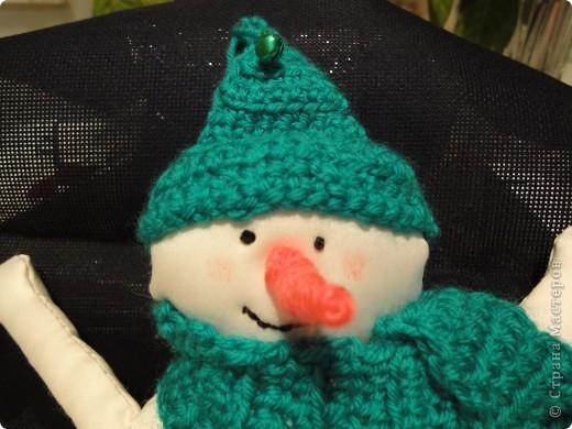 У нашего снеговика вязаная крючком шапка с бубенчиками и шарфик с кистями. А еще нос-морковка. Внутри проволочный каркасик, на который намотана нить. фото 2