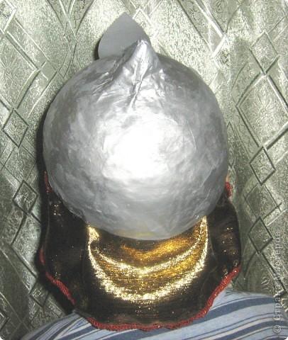 """Мой братик на этом Новом году был богатырём. Мы с мамой сделали ему шлем.  Сначала надо надуть воздушный шарик нужной глубины, и нужного диаметра.( померить голову). Затем делаем папье-маше. 1-ый слой мокрая газетная бумага, последующие слои бумага+клейстер. Примерить, если всё в порядке приклеить сверху шлема конус из плотной бумаги и целиком всю """"каску"""" покрываем ещё одним слоем папье-маше. Сушим. Красим серой гуашью с двух сторон. Снова сушим. Красим серебряной краской, лучше с двух сторон( чтобы волосы гуашь не пачкала)). Из серебряного картона вырезаем отделочную деталь, приклеиваем и росписываем гуашью. Прямоугольный кусочек золотой ткани ( в цвет кольчуги) слегка собирая на сборку приклеиваем пистолетом к обратной стороны шлема сзади. Всё. фото 3"""