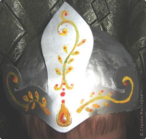 """Мой братик на этом Новом году был богатырём. Мы с мамой сделали ему шлем.  Сначала надо надуть воздушный шарик нужной глубины, и нужного диаметра.( померить голову). Затем делаем папье-маше. 1-ый слой мокрая газетная бумага, последующие слои бумага+клейстер. Примерить, если всё в порядке приклеить сверху шлема конус из плотной бумаги и целиком всю """"каску"""" покрываем ещё одним слоем папье-маше. Сушим. Красим серой гуашью с двух сторон. Снова сушим. Красим серебряной краской, лучше с двух сторон( чтобы волосы гуашь не пачкала)). Из серебряного картона вырезаем отделочную деталь, приклеиваем и росписываем гуашью. Прямоугольный кусочек золотой ткани ( в цвет кольчуги) слегка собирая на сборку приклеиваем пистолетом к обратной стороны шлема сзади. Всё. фото 2"""