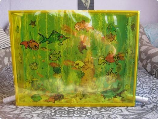 """Корпус аквариума сделан из оконных деревянных штапиков, обклеен прозрачной цветной плёнкой. Водоросли - из зелёной пряжи """"травка"""". Рыбки нарисованы витражными красками, вырезаны и подвешены на нитках. На задней стенке декупаж и роспись фломастерами. По бокам вставлены фонарики, которые освещают морское дно и водоросли. фото 1"""