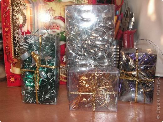 Мне перед новым годом попали в руки пустые пластиковые коробочки из-под игрушек.А потом пришло время украшать к новому году клуб.Эта идейка пришла мне в голову,получилось украшение почти из ничего:остатки мишуры( захотелось разделить ее по цвету),обрезок блестящей ленточки и те самые коробочки.Маленькие пошли на елку,побольше встали под нее.Все вместе слегка завораживает...