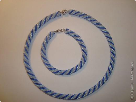 Для браслета набираем 1,1 м. , для колье 2,4 м. бисера в следующей последовательности: 1 синяя бусинка, 1 голубая, 1 белая. Затем крючком 1,25мм. делаем петельку и одну воздушную петлю, далее вяжем по МК, ввязывая по 6 бусинок в один ряд.