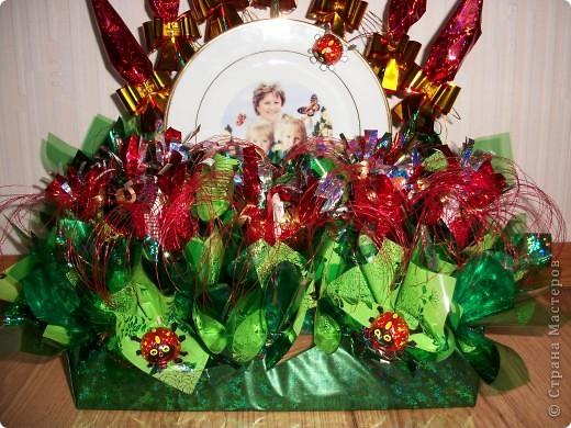 Моя свекровь очень хотела фотографию двух своих внучек, а еще она большая сластена. Вот мы и решили все это соединить и подарить на День рождение. Так появилась такая композиция. В центре тарелочка, которую мы делали на заказ. (фото нашей бабушки с внучками) и конечно же цветы из конфет.  фото 2
