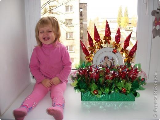 Моя свекровь очень хотела фотографию двух своих внучек, а еще она большая сластена. Вот мы и решили все это соединить и подарить на День рождение. Так появилась такая композиция. В центре тарелочка, которую мы делали на заказ. (фото нашей бабушки с внучками) и конечно же цветы из конфет.  фото 3