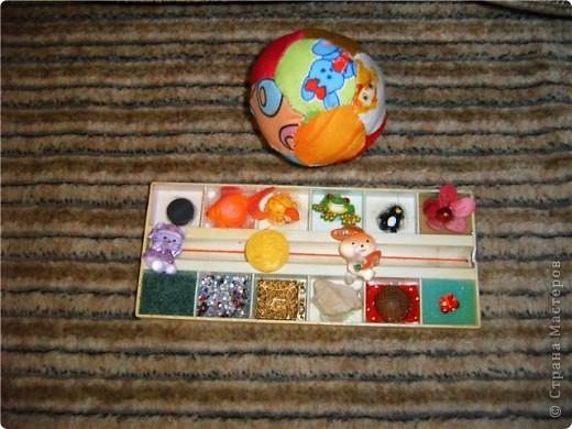 тренажер из красок. наклеила внутрь разные пуговки, игрушки от киндеров,магнит,  это с одной стороны. А с другой стороны - разной фактуры материалы: дерево, пласмассу, железо, поролон, камень, бисер залила клеем. Посередине на веревочке зайка и кошечка кидают друг другу мячик-пуговку. Ну и шитый мячик