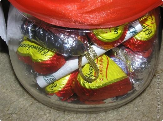 Такую баночку с конфетками и денежкой внутри я сделала в подарок на свадьбу. Захотелось, что-то новенького и необычного. Молодожены были в восторге. Идею подарка в банке я подсмотрела на сайте 7даров. Для изготовления подарка мне понадобилось около 25 конфет, половину из которых я завернула в фольгу. фото 2