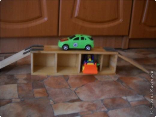 Из дощечек сколотила гараж для сына. Из ремешка от сумки сдалала петли для откидывающегося моста. В сложенном виде занимает совсем мало места