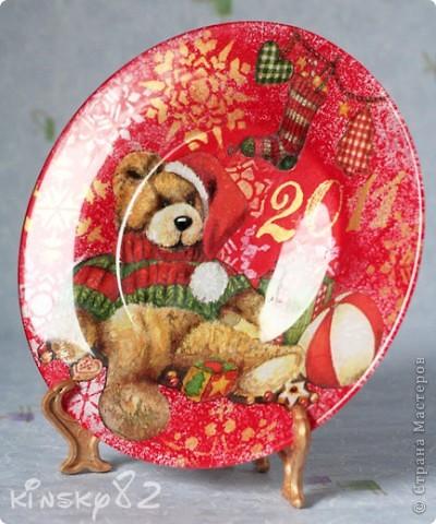 А у меня новая тарелочка. В этот раз празднично-поздравительно-новогодняя. Была подарена маме мужа на Новый 2011 год! Выполнена в технике обратного декупажа. Картинка как и всегда обычная трёхслойная салфеточка. Посудинка раскрашена акриловыми красками. Снежинки нанесены с обратной стороны тарелЬки с помощью трафаретов золотым и серебряным контурами по стеклу. Кстати, тарелочка вскрыта стекловидным лаком, так что водички она вовсе не боится и её смело можно мыть! А еще с неё можно есть, но мама как всегда будет на неё только любоваться... фото 1
