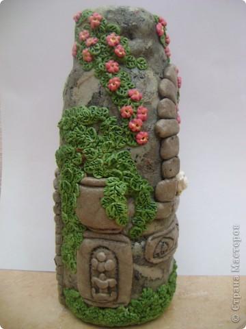 каменный вазон с растением, и ветка цвтущего шиповника фото 1