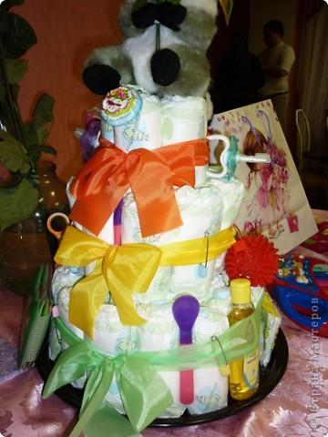 Недавно моей племяннице исполнился 1 годик! Ей подарили вот такой замечательный торт. Работа замечательного творческого человека Екатерины Беленькой, которая и сделала такой неожиданный подарок. От такого торта все гости были просто в восторге, не говоря уже об самой имениннице, которая тут же потянулась к разнообразным вещичкам, привязанных к торту.    С разрешения Екатерины, выкладываю эту работу здесь, для вашего обозрения, может и вы решите сделать своим близким и родным такой подарок.    Весь торт сделан из памперсов, скрученных в трубочку. На ленточках привязаны самые необходимые для младенца вещи (ватные палочки, масло для кожи, ложечки, щеточки, массажный мячик и т.д) Внутрь торта был вложен сюрприз, который известен только имениннице.  Старалась сфотографировать со всех сторон, специально для Страны Мастеров!  фото 1