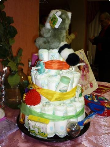 Недавно моей племяннице исполнился 1 годик! Ей подарили вот такой замечательный торт. Работа замечательного творческого человека Екатерины Беленькой, которая и сделала такой неожиданный подарок. От такого торта все гости были просто в восторге, не говоря уже об самой имениннице, которая тут же потянулась к разнообразным вещичкам, привязанных к торту.    С разрешения Екатерины, выкладываю эту работу здесь, для вашего обозрения, может и вы решите сделать своим близким и родным такой подарок.    Весь торт сделан из памперсов, скрученных в трубочку. На ленточках привязаны самые необходимые для младенца вещи (ватные палочки, масло для кожи, ложечки, щеточки, массажный мячик и т.д) Внутрь торта был вложен сюрприз, который известен только имениннице.  Старалась сфотографировать со всех сторон, специально для Страны Мастеров!  фото 2