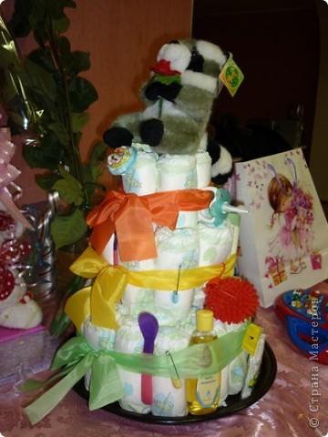 Недавно моей племяннице исполнился 1 годик! Ей подарили вот такой замечательный торт. Работа замечательного творческого человека Екатерины Беленькой, которая и сделала такой неожиданный подарок. От такого торта все гости были просто в восторге, не говоря уже об самой имениннице, которая тут же потянулась к разнообразным вещичкам, привязанных к торту.    С разрешения Екатерины, выкладываю эту работу здесь, для вашего обозрения, может и вы решите сделать своим близким и родным такой подарок.    Весь торт сделан из памперсов, скрученных в трубочку. На ленточках привязаны самые необходимые для младенца вещи (ватные палочки, масло для кожи, ложечки, щеточки, массажный мячик и т.д) Внутрь торта был вложен сюрприз, который известен только имениннице.  Старалась сфотографировать со всех сторон, специально для Страны Мастеров!  фото 3