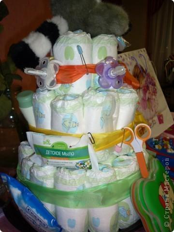 Недавно моей племяннице исполнился 1 годик! Ей подарили вот такой замечательный торт. Работа замечательного творческого человека Екатерины Беленькой, которая и сделала такой неожиданный подарок. От такого торта все гости были просто в восторге, не говоря уже об самой имениннице, которая тут же потянулась к разнообразным вещичкам, привязанных к торту.    С разрешения Екатерины, выкладываю эту работу здесь, для вашего обозрения, может и вы решите сделать своим близким и родным такой подарок.    Весь торт сделан из памперсов, скрученных в трубочку. На ленточках привязаны самые необходимые для младенца вещи (ватные палочки, масло для кожи, ложечки, щеточки, массажный мячик и т.д) Внутрь торта был вложен сюрприз, который известен только имениннице.  Старалась сфотографировать со всех сторон, специально для Страны Мастеров!  фото 4