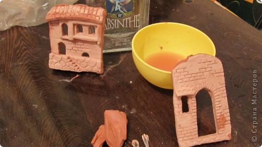1.Из быстрозатвердевающей глины лепим фасад дома(Мы вырезали из цельной пластины,раскатали примерно в 1см,и уже стеками вырезали козырьки,наносили узор кирпича и на фундаменте каменную кладку)прикладываем к бутылке,чтобы глина приняла ее форму и даем высохнуть полностью фото 1