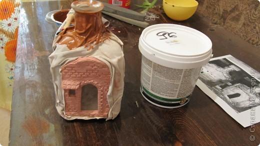 1.Из быстрозатвердевающей глины лепим фасад дома(Мы вырезали из цельной пластины,раскатали примерно в 1см,и уже стеками вырезали козырьки,наносили узор кирпича и на фундаменте каменную кладку)прикладываем к бутылке,чтобы глина приняла ее форму и даем высохнуть полностью фото 3