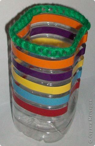 Вот такую коробочку можно сделать из пластиковой бутылки. Отрезаем верх - третью часть. От верха отступаем 7 -10 миллиметров и прокалываем по окружности шилом дырочки через 5 -6 мм. Обшиваем верх нитками для вязания. Вырезаем полоски из самоклейки шириной 10 мм и наклеиваем их по окружности коробочки. Емкость для хранения мелкой мозаики готова. фото 1