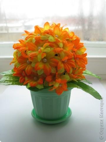 Сделала цветочный шар в подарок сестренке. Купила 4 букетика искусственных цветов, разобрала на отдельные цветочки, соединила по два (сверху желто-оранжевые, а за ними желтые), украсила серединки бусинками. Все это наклеила с помощью клея на заготовленный из бумаги и обмотанный нитками шар, который покрасила акриловой краской фото 1