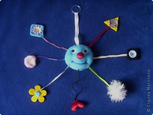 Встречала несколько вариантов на просторах интернета, потом поскребла по сусекам и, из того что удалось найти, создала свой вариант. Старалась чтобы все было разным на вид и наощупь. В голове зашит бубенчик, в розовом двухцветном кружочке - бисер, сердечко пришито к резинке. Размер головы 12см в диаметре, вместе с ножками - 50см.  Единственный минус этой игрушки - слижком тонкие ножки, путаются, а вот в подвешенном состоянии нормально. Если б я делала еще одного, то, конечно, выбрала бы веревочки потолще. Опыт дело наживное! фото 1