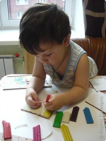 """Знакомьтесь - мой сын Саша. Иззучает пластилин. Хотим поделиться со всеми своим опытом. Итак, нам понадобились: пластили и картон. Сначала мы потренировались в """"размазывании пластилина по ненужному кусочку картона. а потом перешли к самой работе.  Общими усилиями покрыли верхнюю часть картона белым пластилином, а нижнюю - жёлтым. Вот Саша старательно мажет его на картонку. фото 2"""